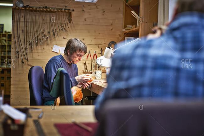 Violin maker in his workshop restoring a scroll