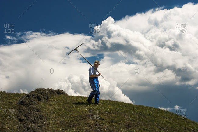 Austria, Radstadt, farmer on field, upcoming thunderstorm in the background