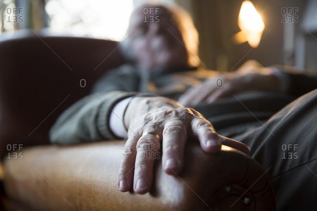 Senior man relaxing in armchair, detail