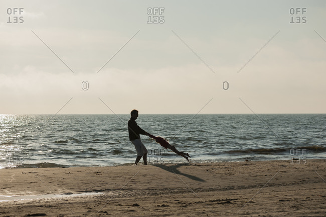 Denmark, Jutland, Lokken, father playing with daughter on beach
