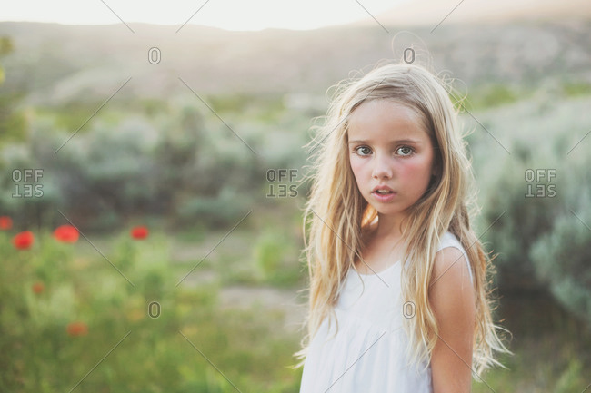 Half length portrait of a blonde girl standing on the meadow