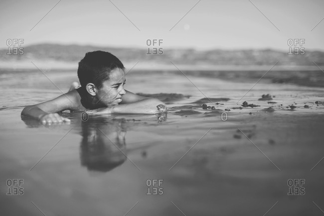 Boy lying in the shallow water