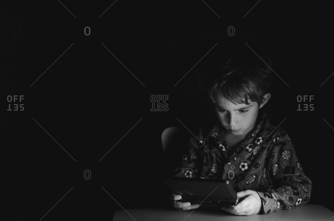 Boy in pajama playing on handheld game console
