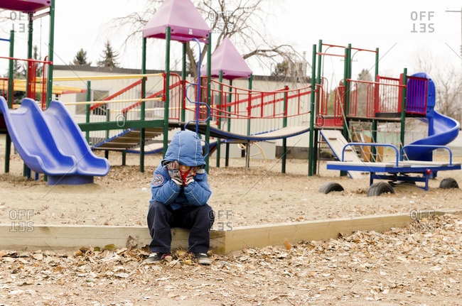 Sad boy sitting on playground