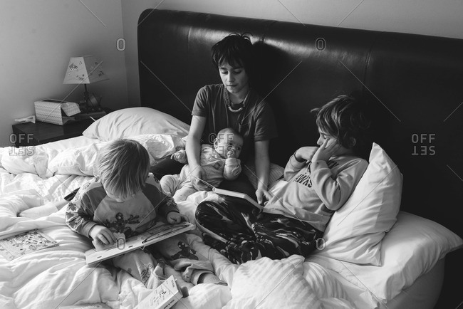 Children reading together in bed