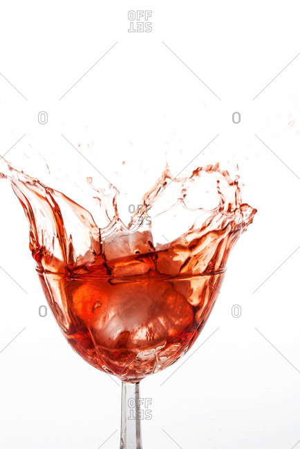 Ice cubes falling into red cocktail