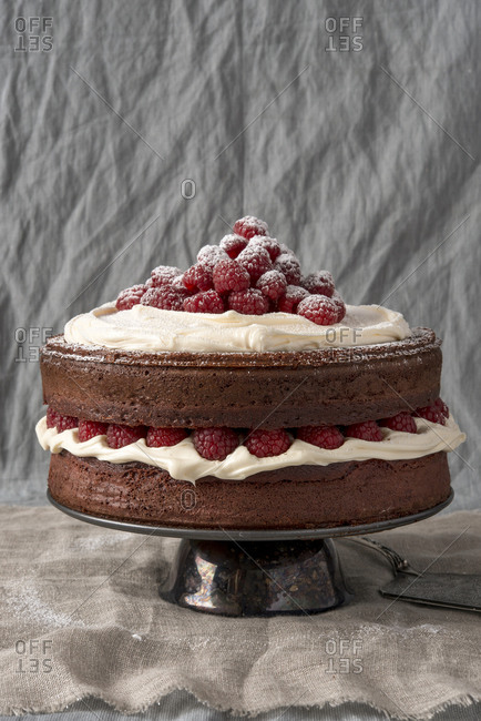 Red velvet cake with raspberries and drizzled icing sugar