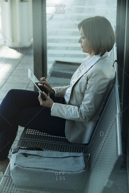 Business woman using tablet computer while waiting on platform