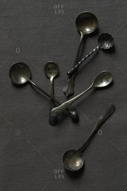 Antique spoons displayed on gray background