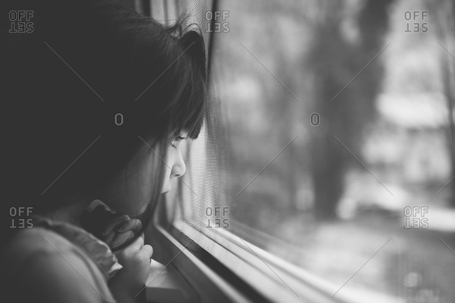 Young girl looking through the window