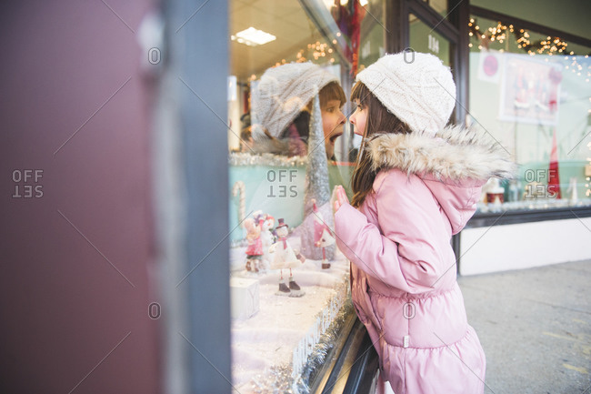 Excited girl watching vitrine decorated for Christmas