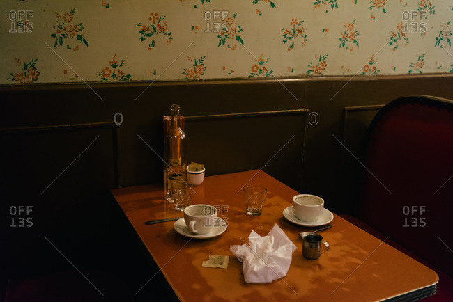 Empty cups and glasses on a table at a diner