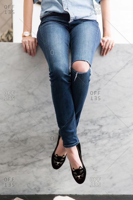 Woman sitting on a parapet in ripped jeans