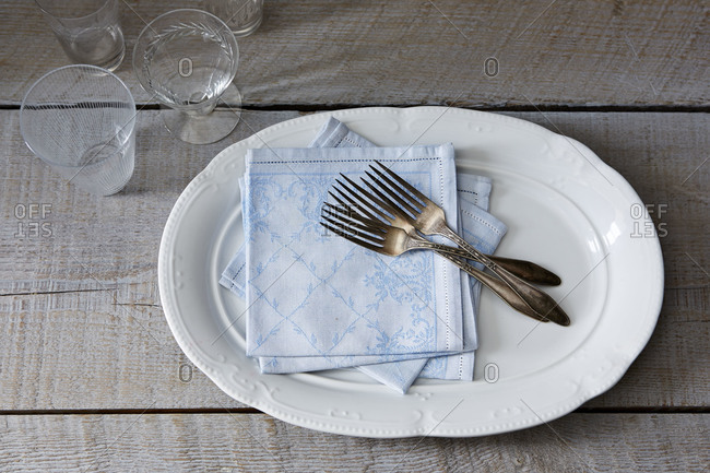 Blue napkins, glasses and forks prepared for laying a table