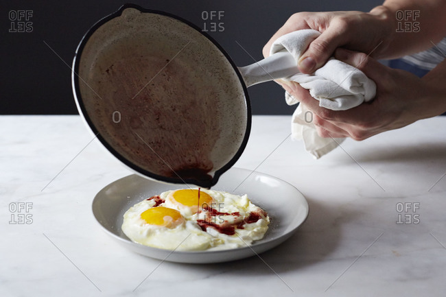 Pouring vinegar onto fried eggs