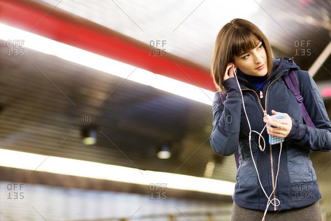 Woman listening to music on a subway platform