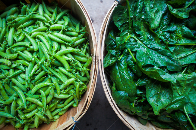 Fresh snap peas and spinach in baskets