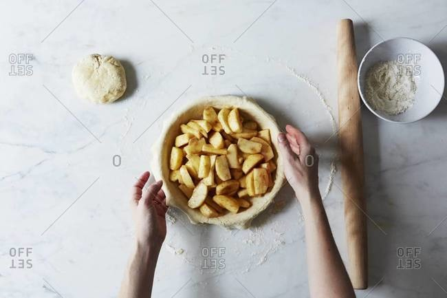 Filling the cream cheese pie crust with apples