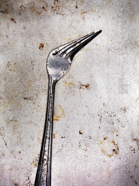 Bent fork on tarnished surface