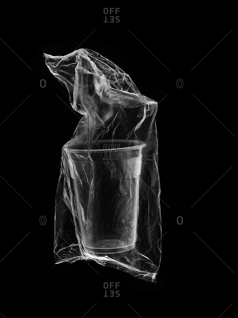 Plastic wrapped disposable cup on black background