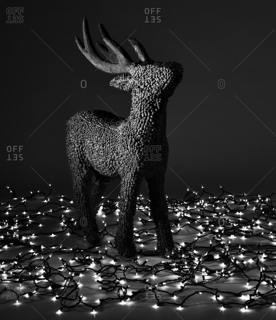 Deer sculpture made of pine cones surrounded by Christmas lights
