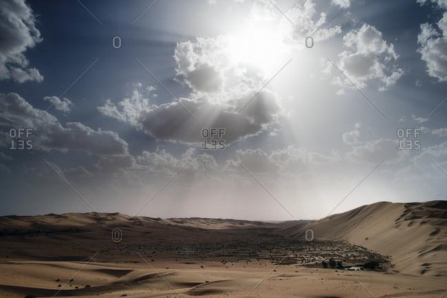 Sun shining through a cloud above a desert