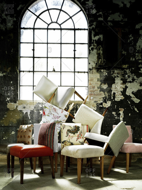 Numerous chairs stacked in a shabby building