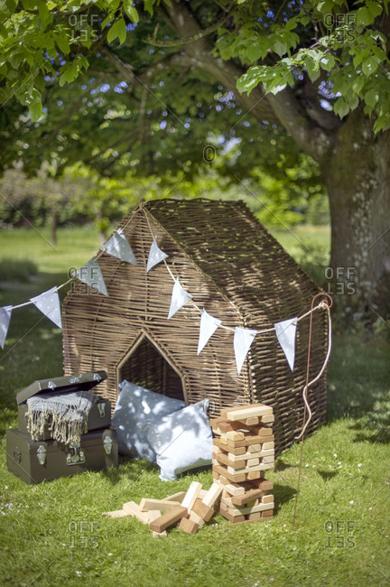 Wicker playhouse, woodblock game and cushions in garden