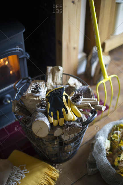 Firewood with gloves and garden tools left by fireplace