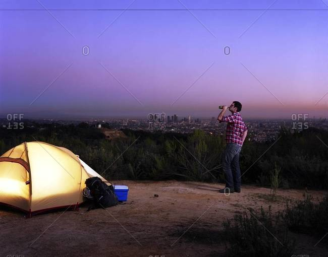 A man drinks beer near a tent