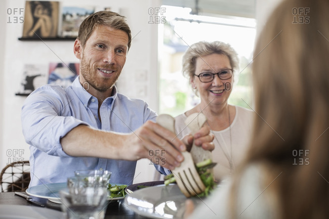 Smiling man serving salad to girl at home