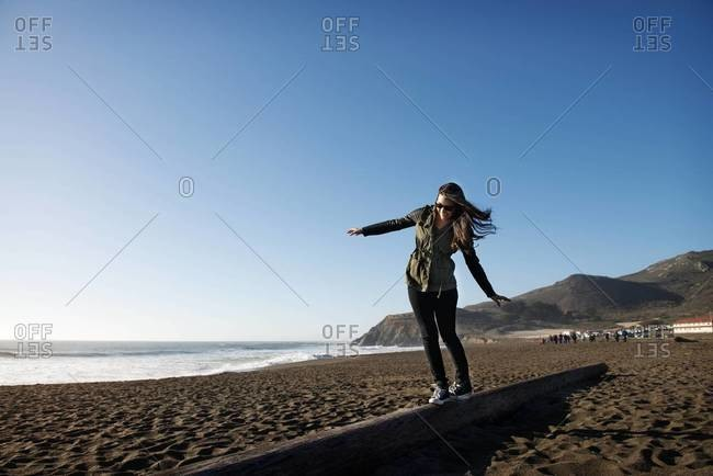 Woman balancing on a tree trunk at the beach