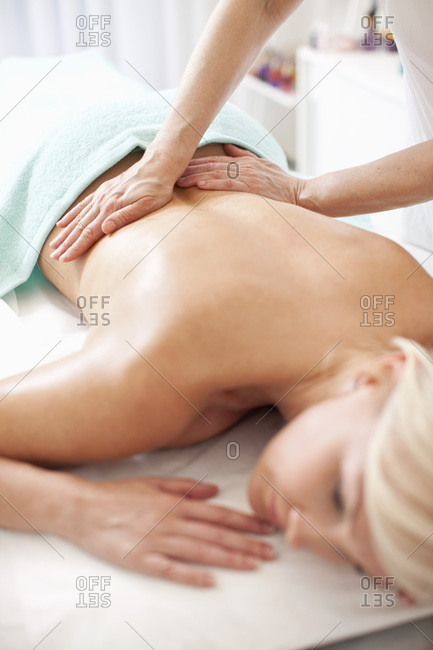 Mid adult woman receiving back massage from masseur at health spa