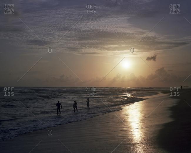 People standing on the seashore at sundown