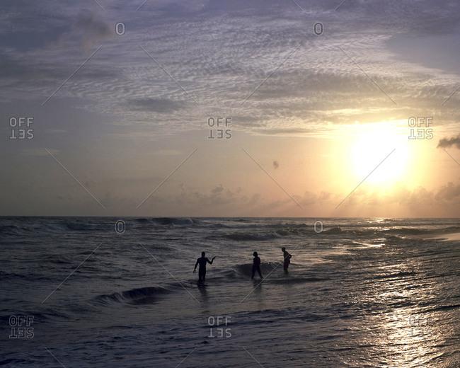 People standing in the ocean at sundown