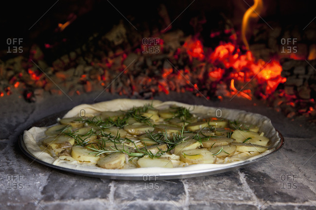 Potato and rosemary pizza in brick oven