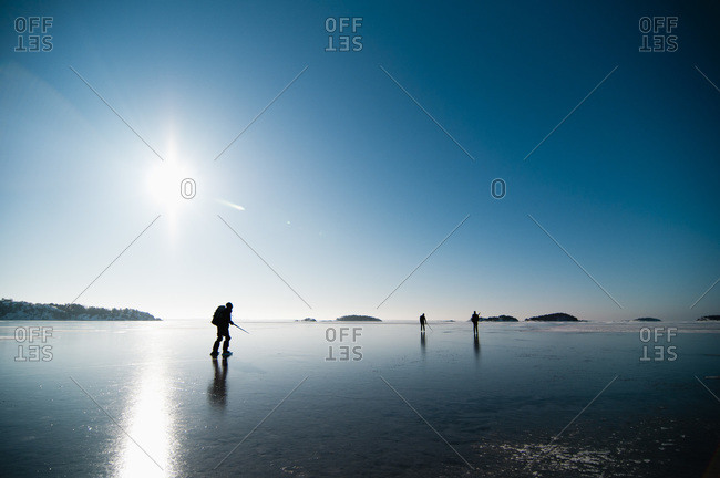 Men on ice with sun beaming from the blue sky