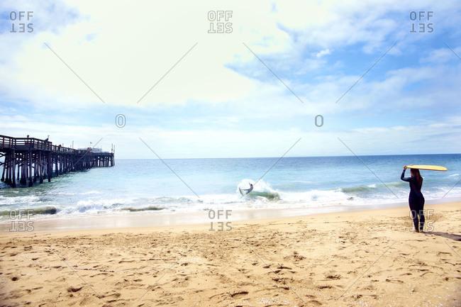Surfers on sandy beach - Offset