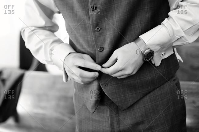 Groom puts on a wedding waistcoat