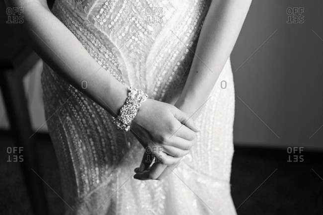 Hands of bride standing in wedding dress