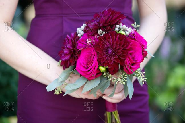 Bridesmaid holding a purple wedding bouquet