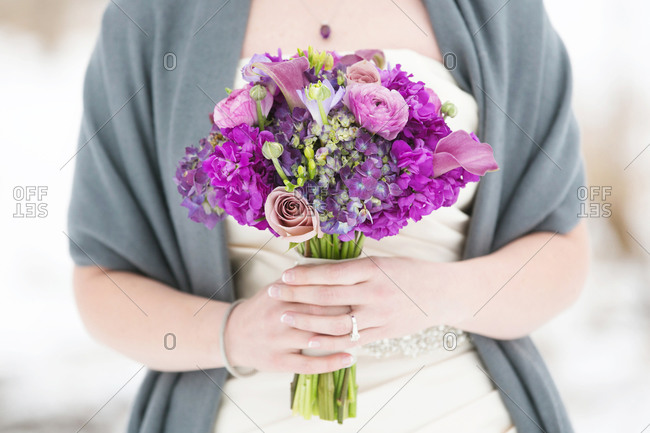 Bride holding purple wedding bouquet