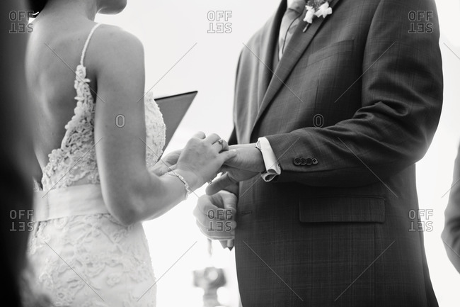 Bride placing a wedding ring on groom's finger