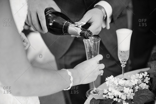 Groom pouring sparkling wine to bride's glass