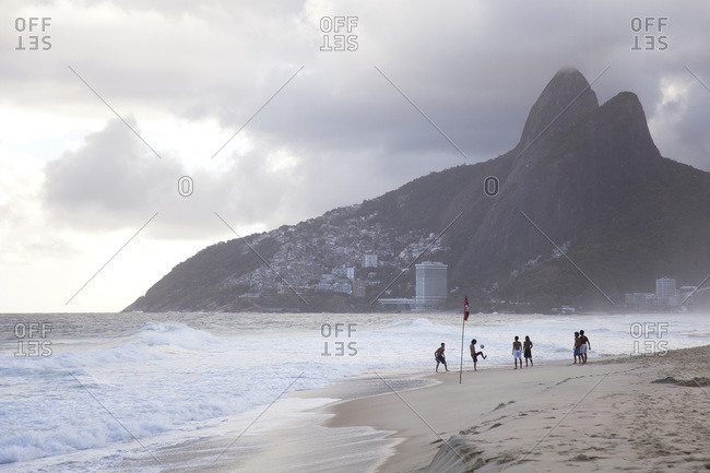 Ipanema Beach Rio de Janeiro, Brazil - April 6, 2014: Group of men playing soccer at the beach