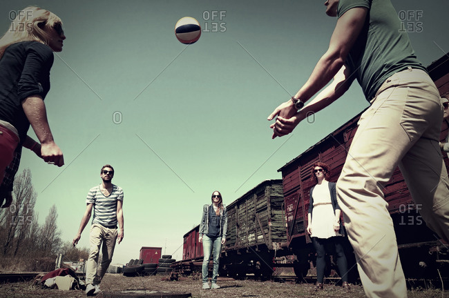 Group of five friends playing volley ball