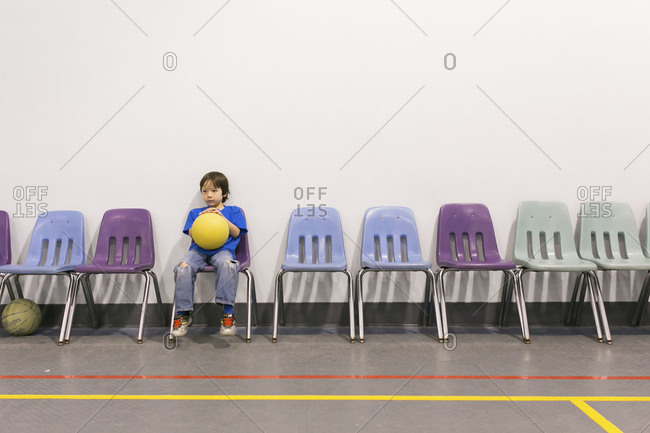 Boy sitting in a gym with a ball in his hands