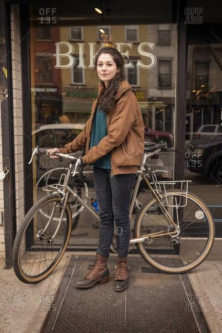 Woman with her brand new bicycle in front of the store