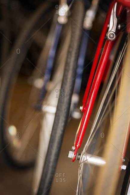 Details of red and blue bicycle\'s tire, fork and spokes