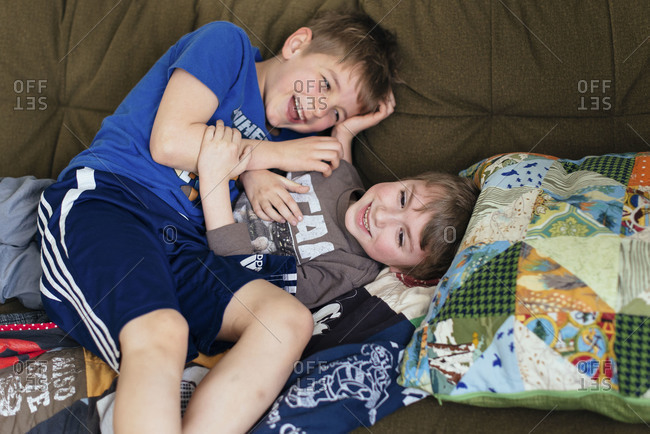 Two boys wrestling on couch